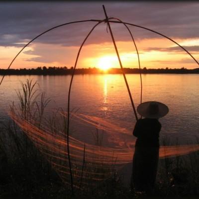 La pêche au fleuve du Mékong au coucher de soleil